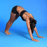 Calf stretch by fit African American woman. Warm up calf stretch exercise on floor by a beautiful young athletic african american fitness woman wearing black Stock Image