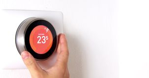 Smart thermostat with a hand setting up the temperature