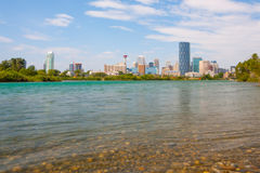 Calgary Cityscape with Bow River in Foreground. A landscape of the city of Calgary with the cool blue water of the Bow river in the foreground Royalty Free Stock Photo