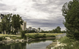 Calgary skyline seen from Bow River. At Prince`s Island Park stock photos