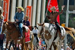 Calgary Stampede Parade 2014. A cowgirls with a traditional red flag of the parade saluting the  spectators Royalty Free Stock Photo