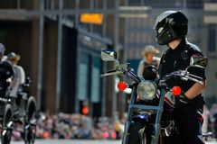 Calgary Stampede Parade - Greatest Outdoor Show on Earth , Calgary ,Alberta , Canada . A policeman  on his motorcycle  in foreground watching the parade Royalty Free Stock Image