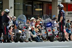 Calgary Stampede Parade - Greatest Outdoor Show on Earth , Calgary ,Alberta , Canada . Two policemen and their bikes in foregroud talking to spectators Stock Images