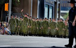 Calgary Stampede Parade 2014- Greatest Outdoor Show on Earth. Canadian Army Regiment greeting and waiving to spectators at parede in background Policeman in Stock Image