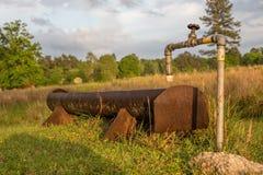 Calha da água no pasto na exploração agrícola fotos de stock royalty free