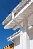 Calha nova da chuva em uma casa branca contra o céu azul Imagem de Stock Royalty Free