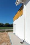 Calha nova da chuva em uma casa com o painel de madeira contra o céu azul Imagem de Stock