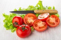 Cali czerwoni pomidory, kawa?ki pomidor, n?? na li?ciach sa?ata na stole obraz royalty free