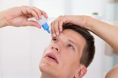 Cali di versamento della medicina dell'uomo nei suoi occhi Immagini Stock