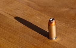 40 caliber bullet. A 40 caliber hollow point bullet on a wooden table with the sun casting a shadow behind it Stock Image