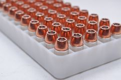 .40 caliber bullets lined up in a container. A plastic bullet container with .40 caliber hollow point bullets on a white background Stock Photo
