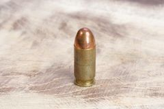 The .45 caliber cartridge. On wooden background Royalty Free Stock Image