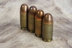 The .45 caliber cartridges. On wooden background Royalty Free Stock Photo