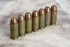 The .45 caliber cartridges. On wooden background Royalty Free Stock Photos
