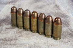 The .45 caliber cartridges on wooden. Background Royalty Free Stock Image