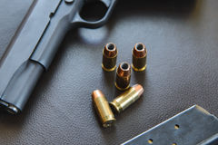 .45 Caliber hollow point bullets near handgun and magazine on le Stock Image