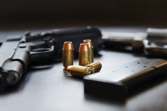 .45 Caliber hollow point bullets near handgun and magazine Stock Photos