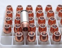 A close up of .40 caliber bullets. 40 caliber hollow point bullets in a plastic shell container with on bullet laying on top of them Stock Images