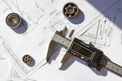 Calibradores electrónicos con los rodamientos en dibujos de una ingeniería Imagenes de archivo