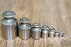 Calibration weight set. On a wooden background Stock Images