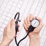 Calibre da pressão sanguínea nas mãos Fotos de Stock Royalty Free