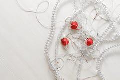 Calibre de carte de voeux fait de différentes tresses et perles argentées, boules rouges sur le fond en bois avec l'espace de cop Photographie stock