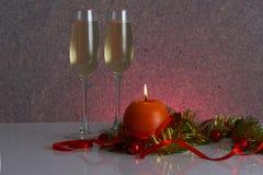 Calibre de carte de voeux fait de tresse d'or et verte avec les boules rouges de Noël, le ruban rouge, la bougie orange et deux v Photographie stock libre de droits
