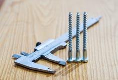 Calibre de glissière et vis en métal sur une surface en bois Photos stock