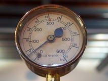 Calibre de pressão redondo de bronze brilhante velho com um seletor redondo marcado nos números e em uma agulha preta do metal fotografia de stock royalty free