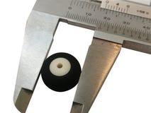 Calibre vernier sur un fond blanc avec une roue images stock