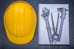 Calibro del divisore della chiave inglese del casco della costruzione del taccuino sulla b Immagine Stock Libera da Diritti