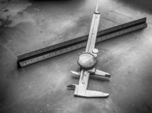 Calibro e righello del quadrante su un banco d'acciaio dell'officina meccanico fotografie stock libere da diritti