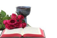 Calice, bibbia e rose su fondo bianco Fotografia Stock