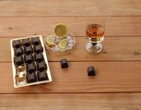 Calice del brandy del limone del cioccolato del whiskey scozzese su un fondo di legno con Fotografia Stock