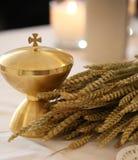 Calice dorato su un altare in una chiesa con le orecchie di grano Immagini Stock Libere da Diritti