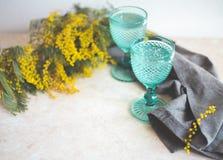 Calici d'annata blu e fiori gialli della mimosa Bicchieri di vino sul fondo del whight fotografie stock