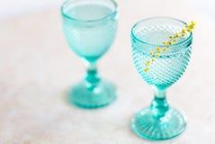 Calici d'annata blu e fiori gialli della mimosa Bicchieri di vino sul fondo del whight fotografia stock