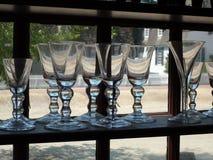 Calici del vetro soffiato della mano nello scaffale della finestra immagini stock libere da diritti