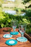 Calici di vetro sui sottobicchieri di lana tricottati in Tray Outdoors di legno Immagine Stock