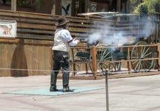 Calicospookstad - cowboy die met kanon schieten Stock Afbeelding