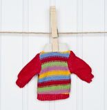Caliente el suéter rayado invierno en una cuerda para tender la ropa Foto de archivo