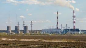 Caliente la estación eléctrica con el campo arado en el primero plano Imagen de archivo libre de regalías