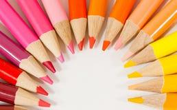 Caliente los lápices coloreados en un arco Fotos de archivo