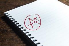 Califique el más de A en el cuaderno Foto de archivo libre de regalías