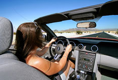 Califoria Roadtrip. Woman driving convertible car on empty road Royalty Free Stock Images