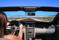 Califoria Roadtrip. Woman driving convertible car on empty road Stock Images