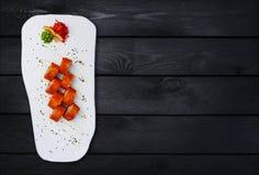 Californië Maki Sushi - Broodje van Krabvlees binnen wordt gemaakt, Avocado, Komkommer die Hoogste mening Zwarte houten achtergro Stock Fotografie