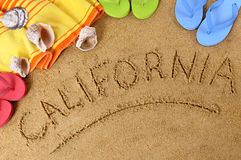 California beach. Beach background with towel and flip flops and the word California written in sand Stock Photos