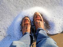 California beach shot of my boots with the sea foam lapping at my feet. For travel blogs as a banner image, graphic, social media royalty free stock photo