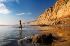California Coast. Boy looks in wonder at the golden cliffs of Torrey Pines State Park near sunset Stock Image